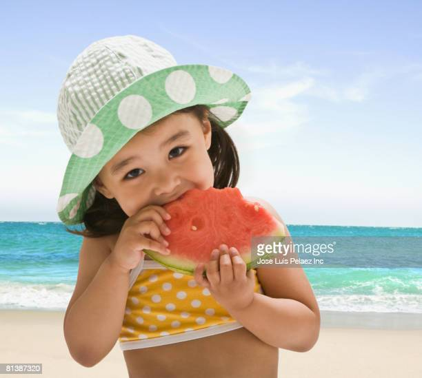 Asian girl eating watermelon at beach