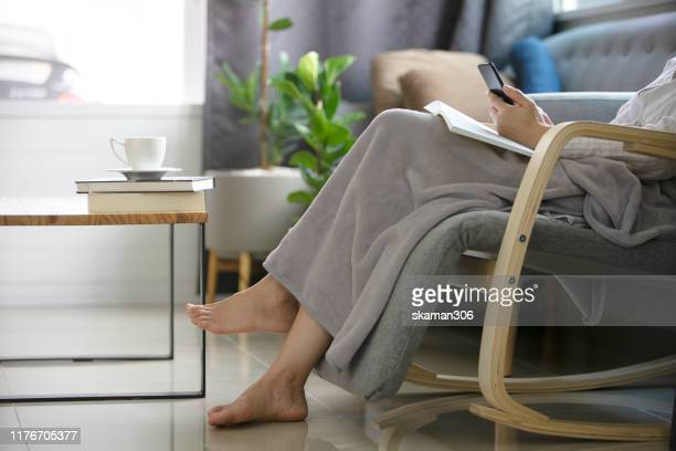asian girl female relax reading a book on cozy sofa with air purifier machine - air respirator mask stock pictures, royalty-free photos & images