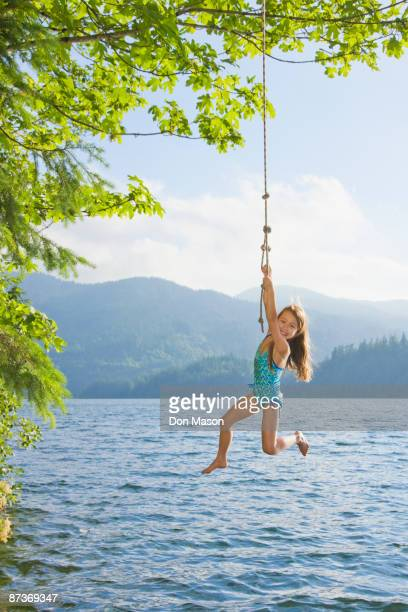 Asian girl hanging from lake rope swing