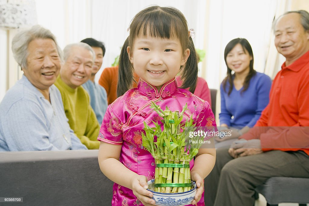 Asian girl holding a pot of lucky bamboo : Stock Photo