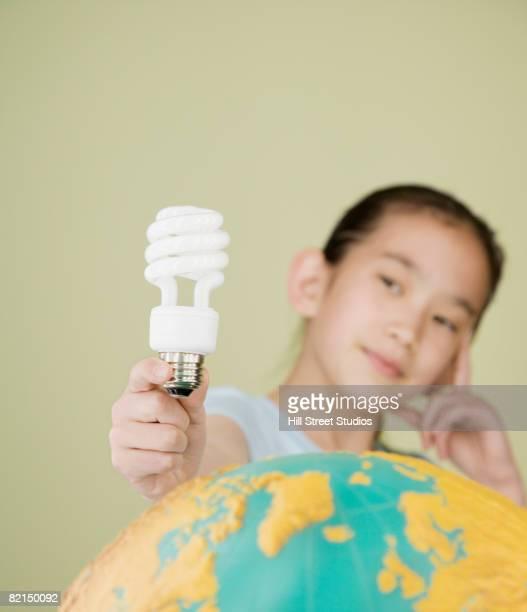 Asian girl holding light bulb over globe