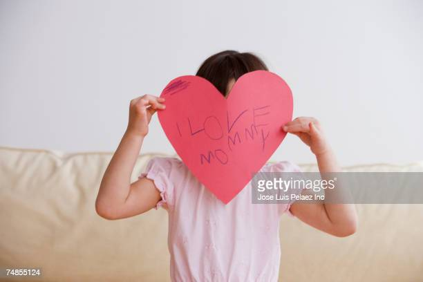 Asian girl holding paper cut out heart for mother