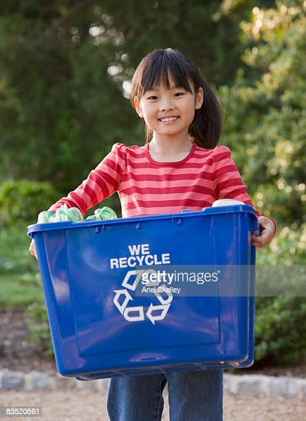 Asian girl holding recycling bin