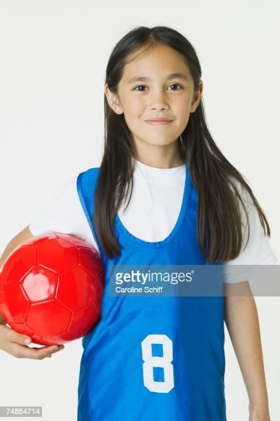 Asian girl holding soccer ball