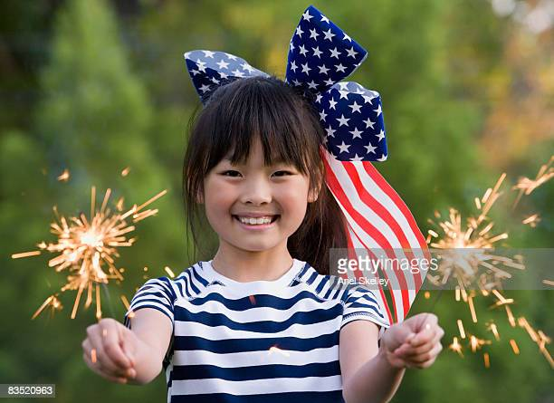 Asian girl holding sparklers on Forth of July