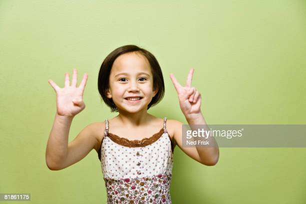 Asian girl holding up six fingers