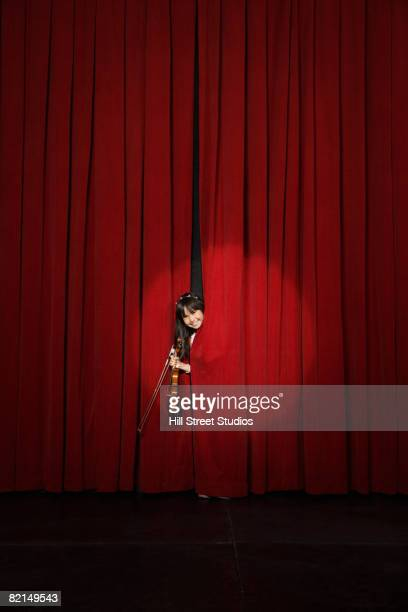 Asian girl holding violin and peeking through curtain