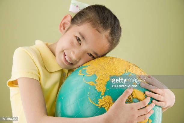 Asian girl hugging globe
