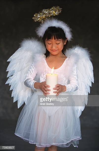 Asian girl in angel costume holding candle