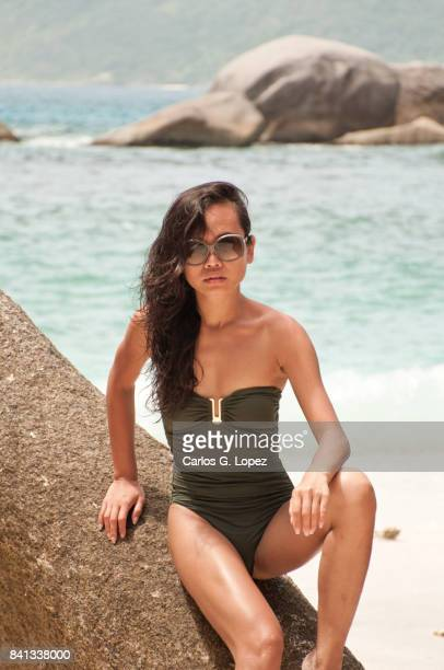 asian girl in green swimming suit and sunglasses sitting on rock - indian bikini stock pictures, royalty-free photos & images