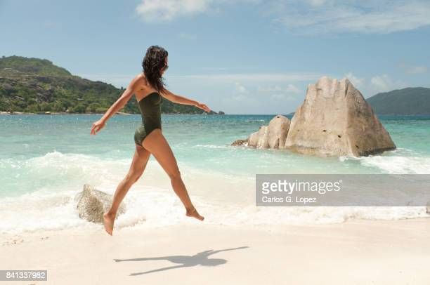 asian girl in green swimming suit jumping on white sand beach - hot indian model stock pictures, royalty-free photos & images