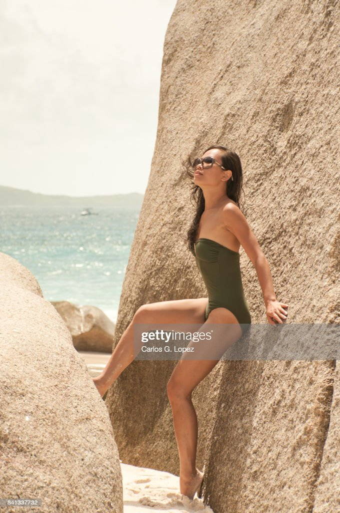 Asian girl in green swimming suit poses on giant rock : Stock-Foto