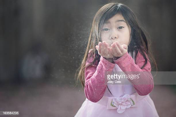 Asian girl in pink dress blows sand from her hands
