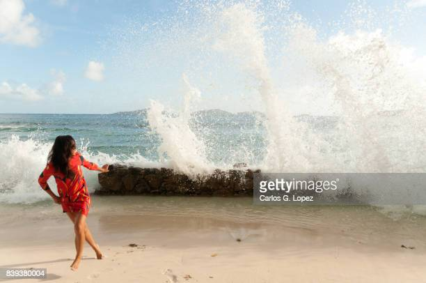asian girl in red dress running from wave - runaway stock photos and pictures