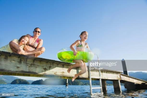 Asian girl jumping in lake