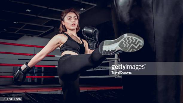 asian girl kick a sand bag in kickboxing gym. young women workout a kick on the punching bag in gym. exercise and muay thai concept - mixed martial arts stock pictures, royalty-free photos & images