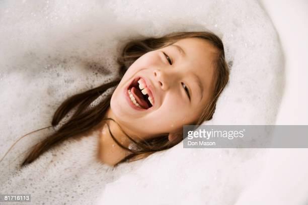 Asian girl laughing in bubble bath