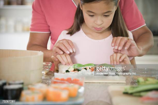 Asian girl learning to make sushi hand roll
