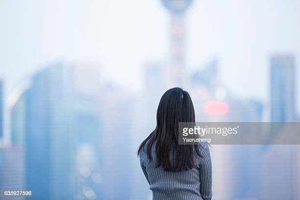 A Asian girl looking at the city sky