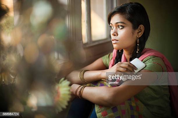 Asian girl next to window with mobile phone looking away.