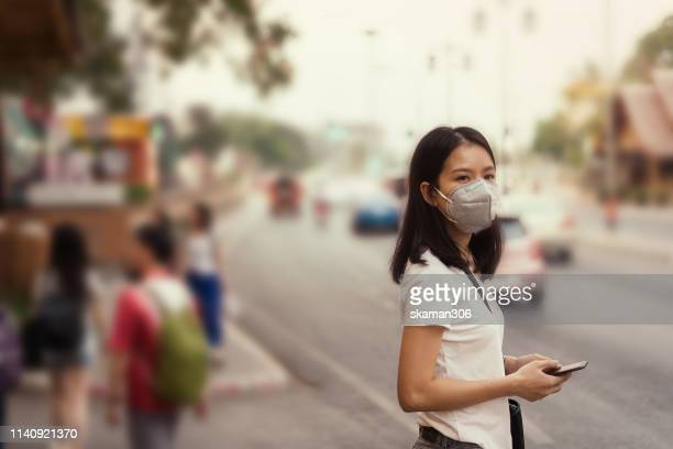 asian girl on street and wearing pm 2.5 mask for safety from air pollution - epidemia foto e immagini stock
