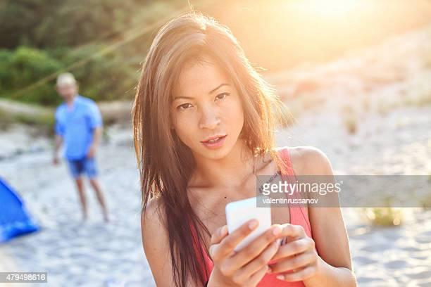 Asiatique fille sur la plage à l'aide de téléphone portable
