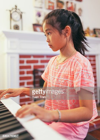 Asian Girl Playing Piano In Living Room Stock Photo | Getty Images