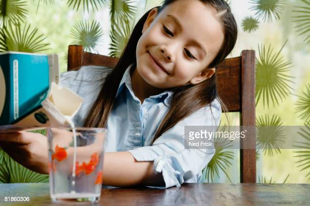 asian girl pouring glass of milk - milk carton stock photos and pictures