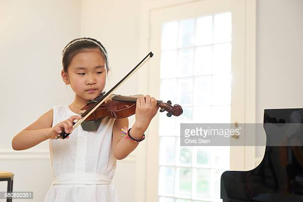 asian girl practicing violin - scarsdale stock photos and pictures