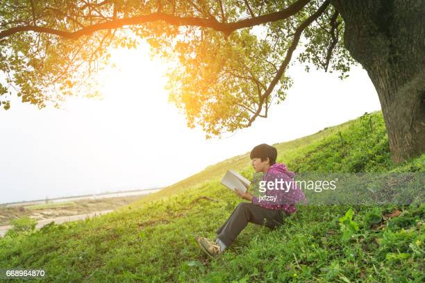 asian girl reading book in outdoor