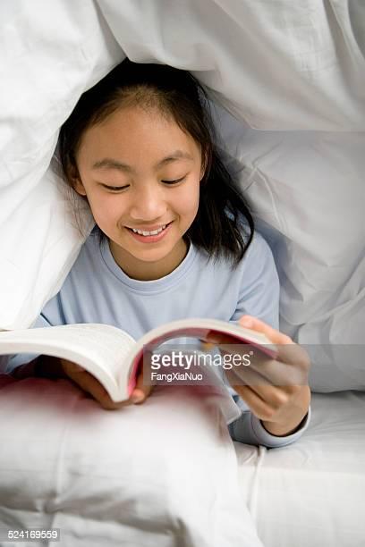 Asian girl reading book secretly