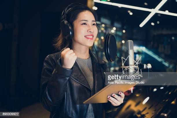 asian girl singing and holding a digital tablet at a recording studio,shanghai,china - singer stock pictures, royalty-free photos & images