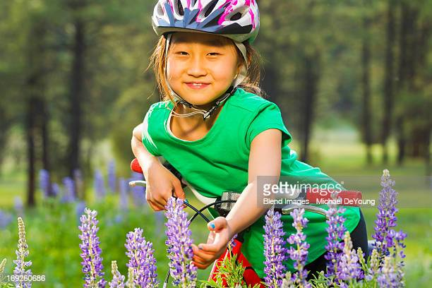 Asian girl sitting on bicycle in meadow