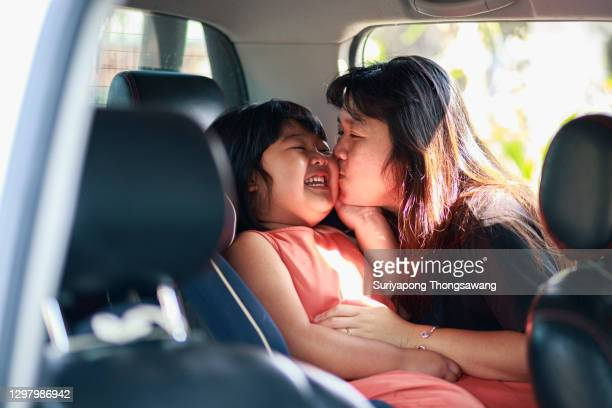 asian girl smile sitting on car safety seat and happy mother kissing her daughter. - thai ethnicity stock pictures, royalty-free photos & images