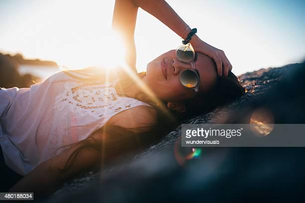 アジアの女の子を笑顔に横たわるロックのビーチ