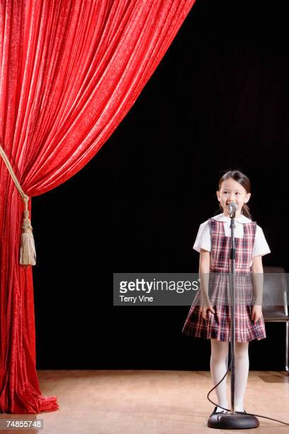 Asian girl speaking into microphone on stage