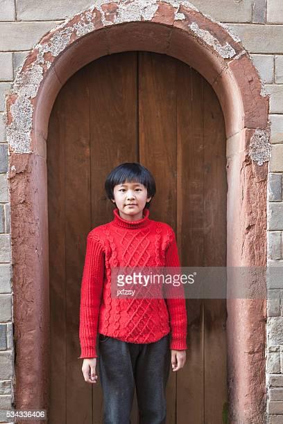 asian girl standing infront of the old door