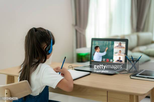 asian girl student video conference e-learning with teacher and classmates on computer in living room at home. homeschooling and distance learning ,online ,education and internet. -  eラーニング ストックフォトと画像