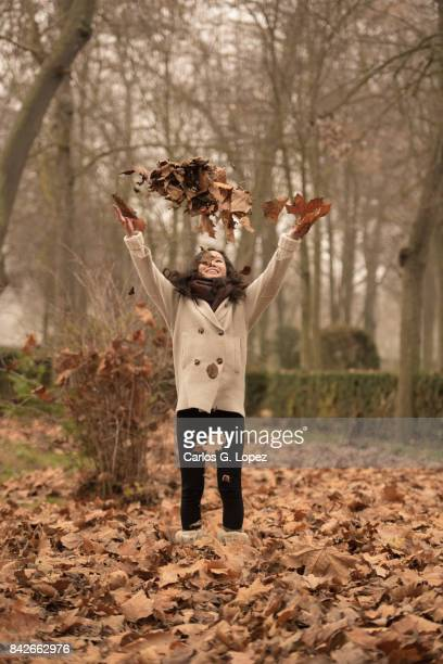 Asian girl throwing dry brown leaves up in the air