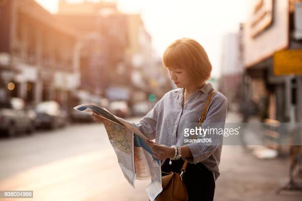 Asian Girl travel with map and use smartphone in urban city