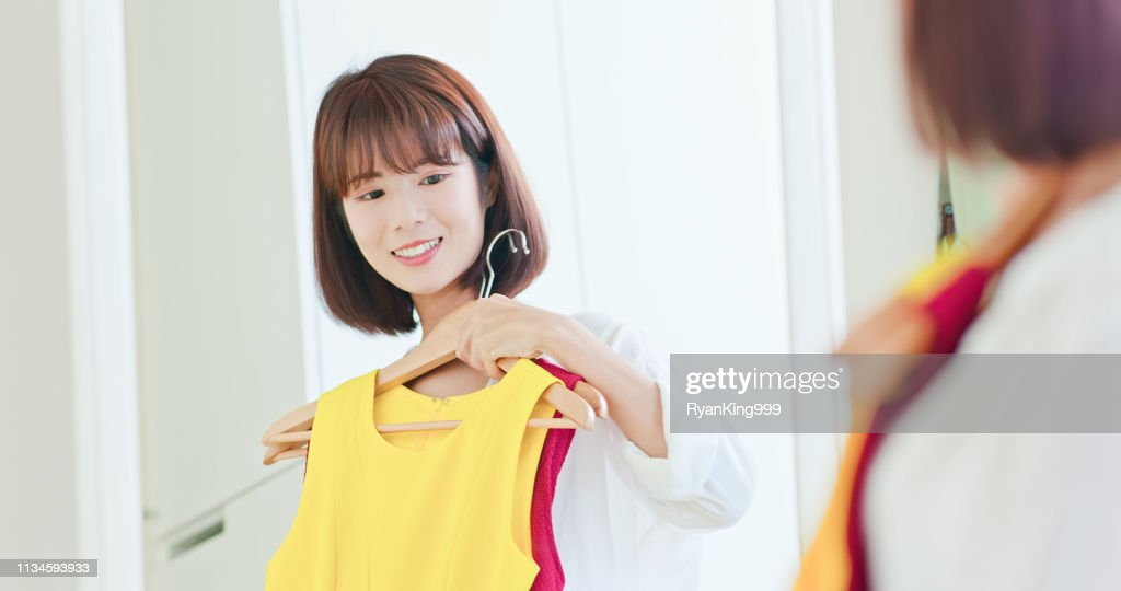 asian girl trying dress happily : Stock Photo