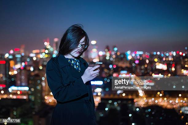 Asian Girl Using A Mobile Phone in Downtown