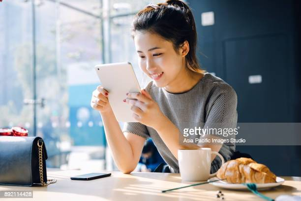 asian girl using digital tablet at cafe,shanghai,china - east asian ethnicity stock pictures, royalty-free photos & images