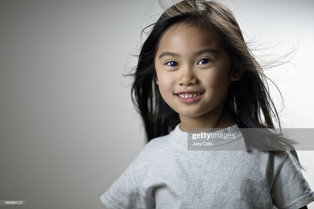 Asian girl wearing a gray t-shirt smiles : Stock Photo