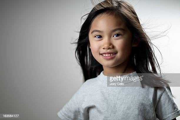 Asian girl wearing a gray t-shirt smiles