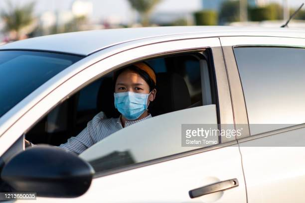 asian girl wearing face mask in a car - driving mask stock pictures, royalty-free photos & images