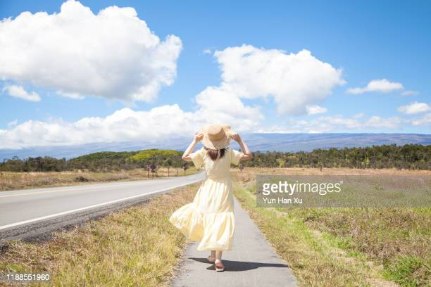 asian girl wearing hat & dress walking on road - long bright yellow dress stock pictures, royalty-free photos & images
