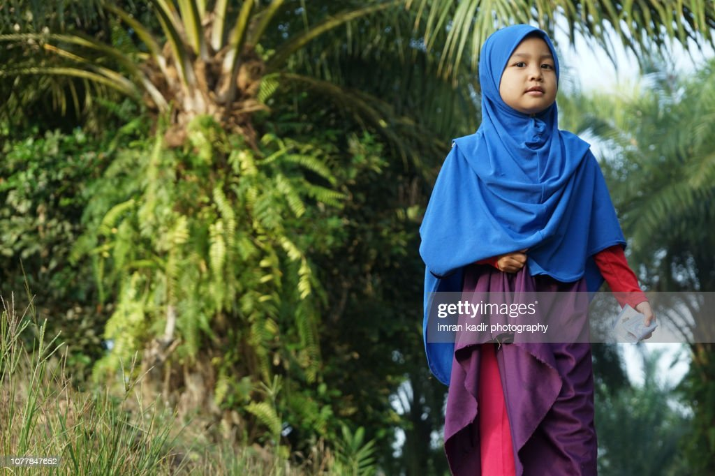 Asian girl wearing hijab standing on the backyard : Stock Photo