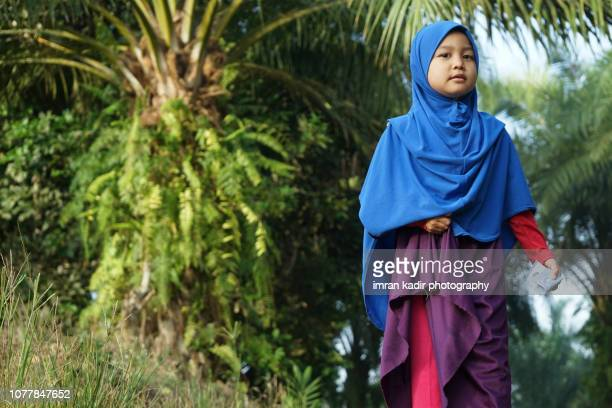 asian girl wearing hijab standing on the backyard - malaysia beautiful girl stock photos and pictures