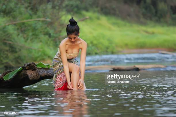 Asian girl wearing Sarong while taking a bath in the river